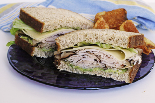 A turkey sandwich on whole grain bread is shown on a purple plate with chips. This post is about how to perk up your turkey sandwich.