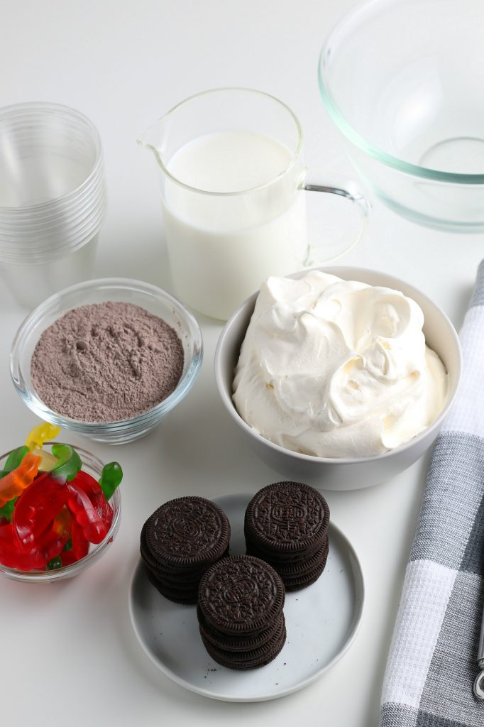 Ingredients for this dirt cups recipe are shown on a white surface.