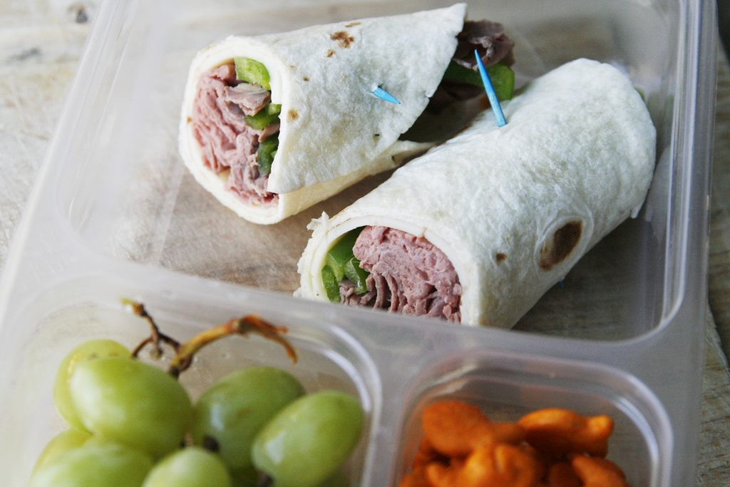 Barbecue Roast Beef Wraps are shown in a plastic container with grapes and Goldfish.