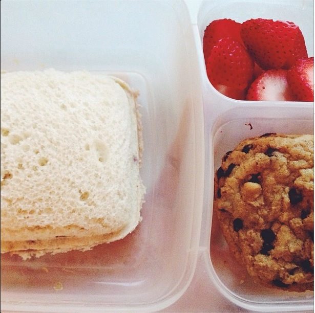 A lunch featuring a sandwich, strawberries and cookies.