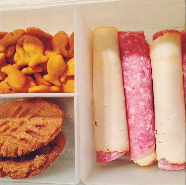 A lunch featuring salami and cheese rollups, Goldfish and cookies.