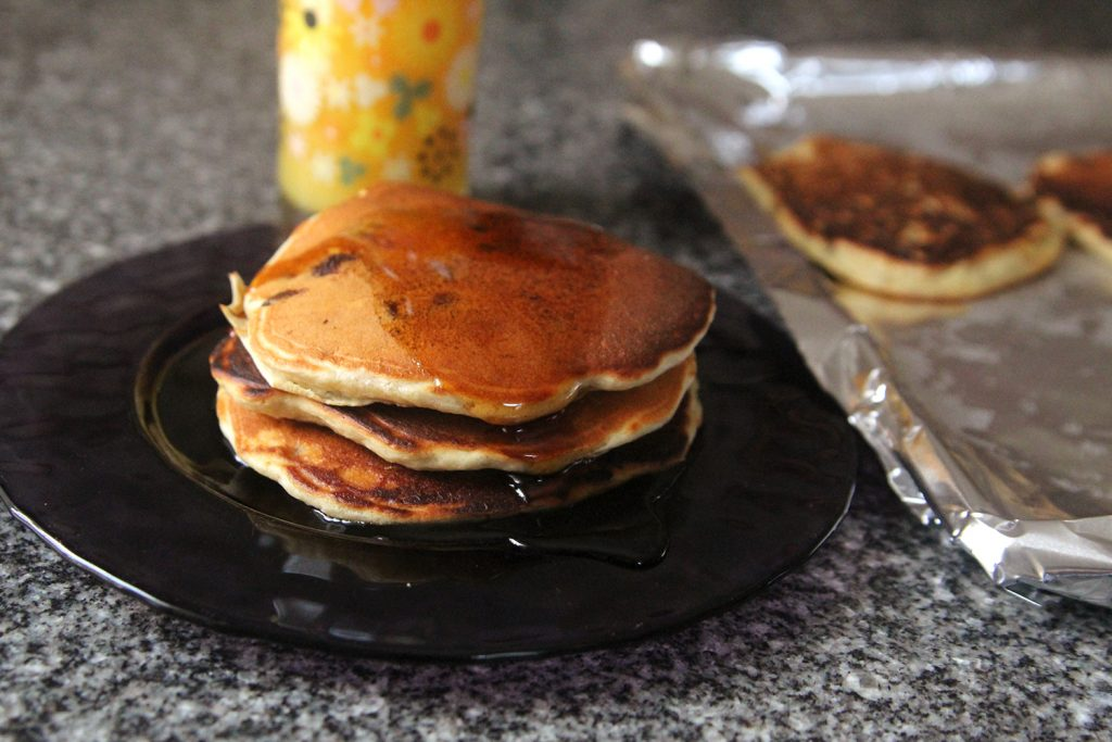 A stack of  Banana Chocolate Chip Pancakes is shown on a purple plate topped with maple syrup. It sits on a granite countertop with a foil-lined baking sheet with more pancakes and a glass of orange juice nearby.