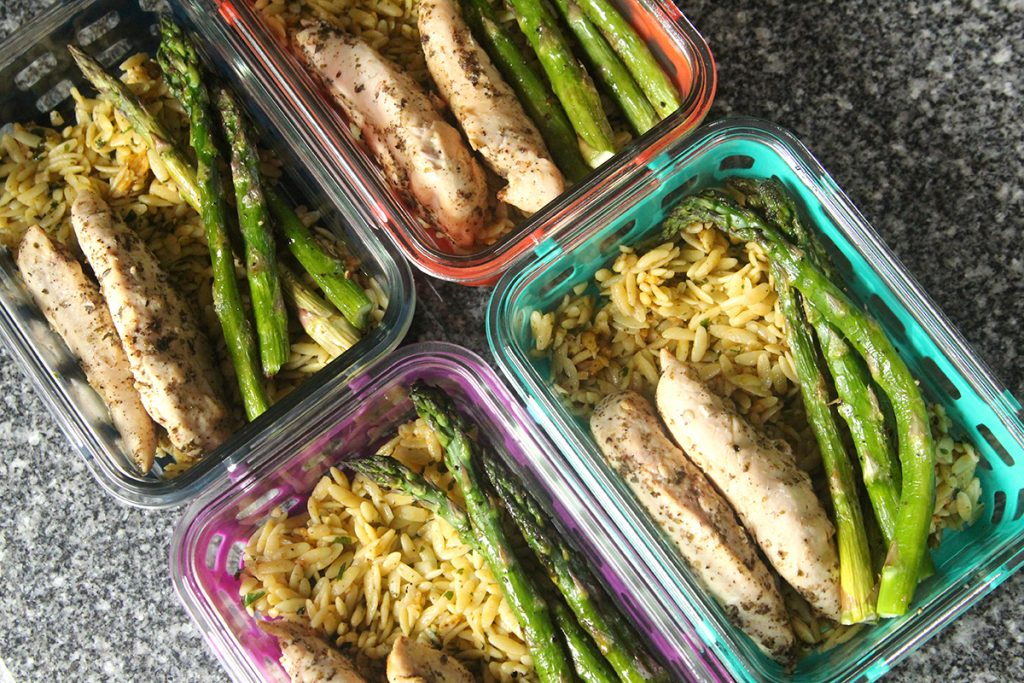 Four colorful glass meal prep bowls are shown. They are all filled with orzo topped with chicken and asparagus.