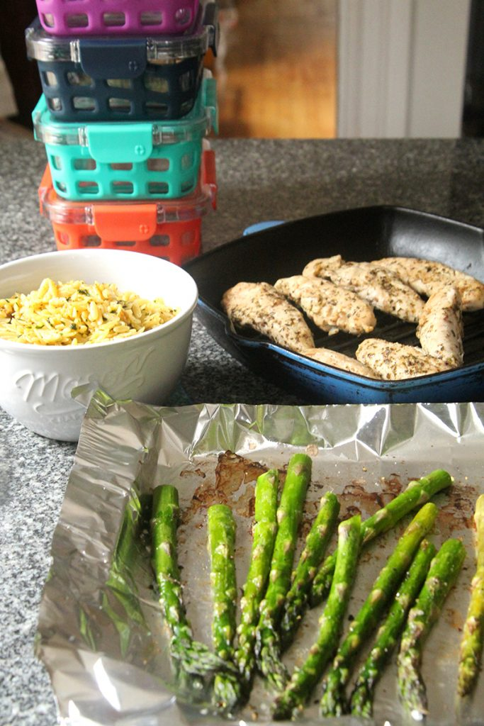 A tray of asparagus, bowl of orzo and pan of chicken are shown on a granite countertop with colorful meal prep bowls in the background.